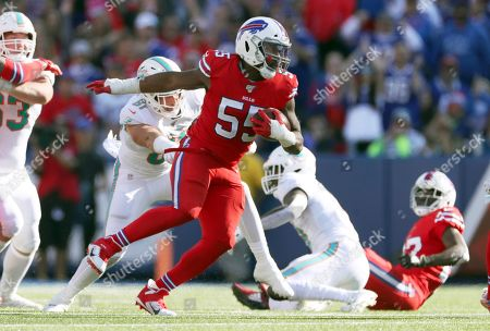 Buffalo Bills defensive end Jerry Hughes carries the ball after recovering a fumble by Miami Dolphins wide receiver Preston Williams in the second half of an NFL football game, in Orchard Park, N.Y