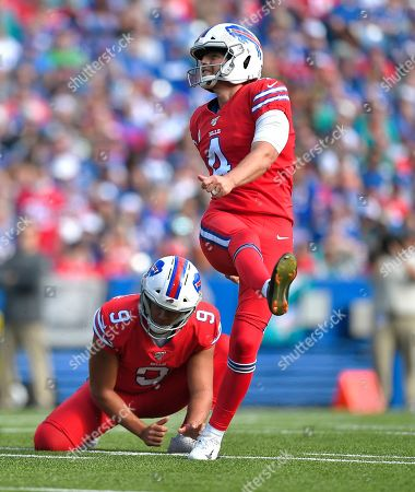 Buffalo Bills kicker Stephen Hauschka follows through on a successful field goal attempt as punter Corey Bojorquez holds in the first half of an NFL football game against the Miami Dolphins, in Orchard Park, N.Y