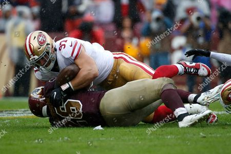Week 13. San Francisco 49ers defensive end Nick Bosa, top, tackles Washington Redskins running back Adrian Peterson in the first half of an NFL football game, in Landover, Md