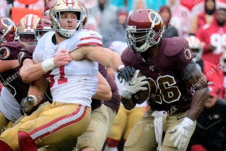 Washington Redskins running back Adrian Peterson (right) runs the ball during an NFL football game against the San Fransisco 49ers, in Landover, Md