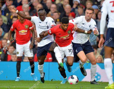 Manchester United's Marcus Rashford (C) in action against Liverpool players Sadio Mane (L) and Jordan Henderson (R) during the English Premier League soccer match between Manchester United and Liverpool FC at Old Trafford in Manchester, Britain, 20 October 2019.