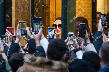 Stock Photo of People take pictures with their mobile phones as US actress Angelina Jolie (C) leaves a shop of French perfumer Guerlain on the Champs-Elysees in Paris, France, 20 October 2019.