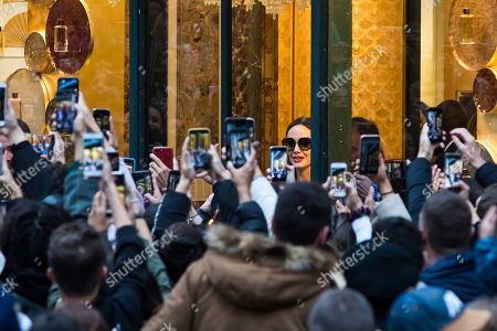 People take pictures with their mobile phones as US actress Angelina Jolie (C) leaves a shop of French perfumer Guerlain on the Champs-Elysees in Paris, France, 20 October 2019.