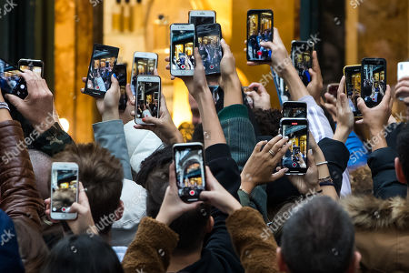 People take pictures with their mobile phones in front of a French perfumer Guerlain shop on the Champs-Elysees as US actress Angelina Jolie (unseen) leaves, in Paris, France, 20 October 2019.