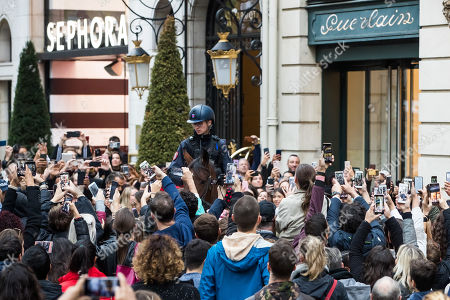 A mounted police officer is surrounded by people taking pictures with their mobile phones as US actress Angelina Jolie (unseen) leaves a shop of French perfumer Guerlain on the Champs-Elysees in Paris, France, 20 October 2019.