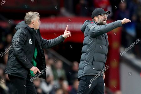 Liverpool's manager Jurgen Klopp, right and Manchester United's manager Ole Gunnar Solskjaer gesture during the English Premier League soccer match between Manchester United and Liverpool at the Old Trafford stadium in Manchester, England