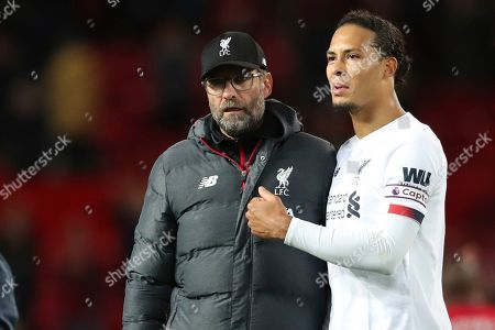 Liverpool's Virgil van Dijk, right and Liverpool's manager Jurgen Klopp greet supporters at the end of the English Premier League soccer match between Manchester United and Liverpool at the Old Trafford stadium in Manchester, England