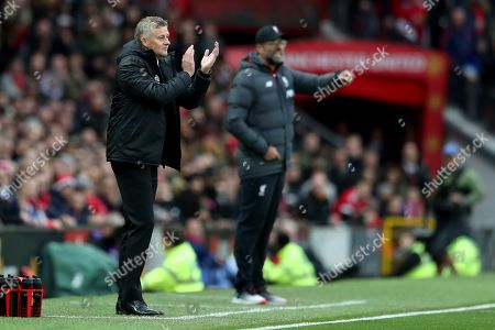 Manchester United's manager Ole Gunnar Solskjaer, left and Liverpool's manager Jurgen Klopp gesture during the English Premier League soccer match between Manchester United and Liverpool at the Old Trafford stadium in Manchester, England