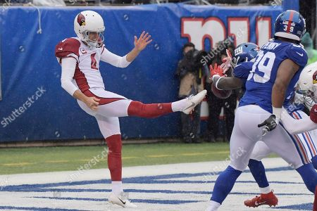 New York Giants defense blocks a punt by Arizona Cardinals punter Andy Lee, left, during the first half of an NFL football game, in East Rutherford, N.J