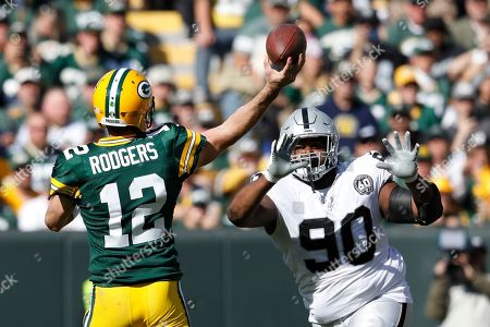 Green Bay Packers' Aaron Rodgers throws a touchdown pass in front of Oakland Raiders' Johnathan Hankins during the first half of an NFL football game, in Green Bay, Wis