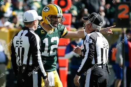 Green Bay Packers' Aaron Rodgers argues a call with side judge Alex Kemp (55) and head linesman Jeff Bergman (32) during the first half of an NFL football game against the Oakland Raiders, in Green Bay, Wis