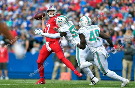 Buffalo Bills quarterback Josh Allen, left, passes under pressure from Miami Dolphins linebackers Jerome Baker (55) and Sam Eguavoen (49) in the first half of an NFL football game, in Orchard Park, N.Y