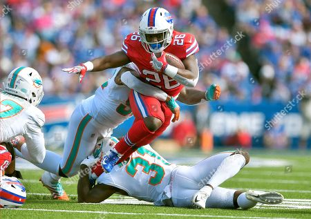 Miami Dolphins linebacker Raekwon McMillan, left, and defensive back Ken Webster, below, tackle Buffalo Bills running back Devin Singletary, center, in the first half of an NFL football game, in Orchard Park, N.Y