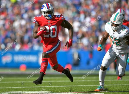 Buffalo Bills running back Frank Gore runs away from Miami Dolphins middle linebacker Raekwon McMillan in the second half of an NFL football game, in Orchard Park, N.Y