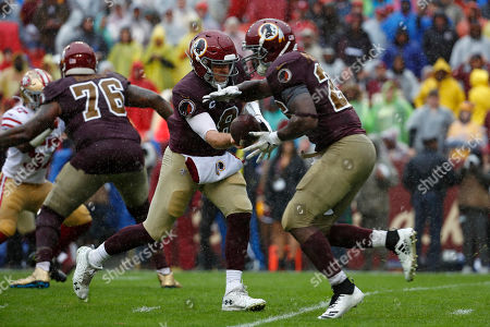 Week 13. Washington Redskins quarterback Case Keenum, center, hands off the ball to Washington Redskins running back Adrian Peterson in the first half of an NFL football game against the San Francisco 49ers, in Landover, Md