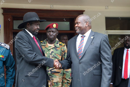 South Sudan's President Salva Kiir left, and opposition leader Riek Machar, right, shake hands after meetings, to discuss outstanding issues to the peace deal. Machar made an impassioned plea to a visiting United Nations Security Council delegation that met with him and President Salva Kiir, to urge speedier progress in pulling the country out of a five-year civil war