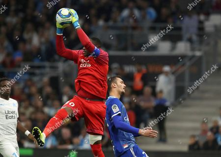 Marseille's goalkeeper Steve Mandanda, front left,makes a save in front of Strasbourg's Ludovic Ajorque during the French League One soccer match between Marseille and Strasbourg at the Velodrome stadium in Marseille, southern France