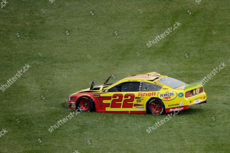 Joey Logano drives across the grass after losing control during a NASCAR Cup Series auto race at Kansas Speedway in Kansas City, Kan