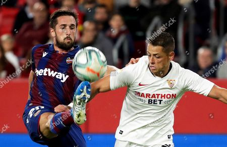 Levante's Jorge Miramon (L) in action against Sevilla's Javier Hernandez 'Chicharito' (R) during the Spanish La Liga soccer match between Sevilla FC and Levante UD at Sanchez Pizjuan stadium in Seville, southern Spain, 20 October 2019.