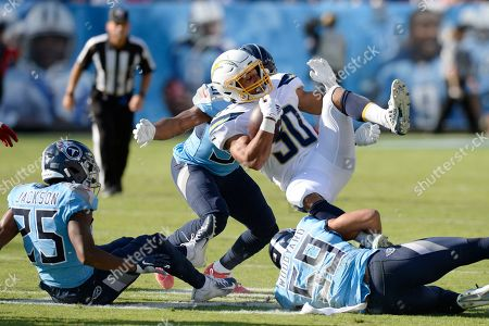 Los Angeles Chargers running back Austin Ekeler (30) is stopped by Tennessee Titans inside linebacker Wesley Woodyard (59) in the first half of an NFL football game, in Nashville, Tenn