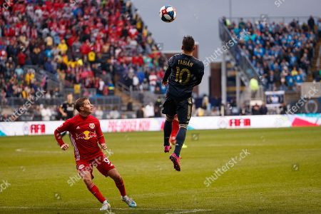 Philadelphia Union's Marco Fabian, right, heads the ball away from New York Red Bulls' Rece Buckmaster, left, during extra time of an MLS soccer Eastern Conference first-round playoff match, in Chester, Pa