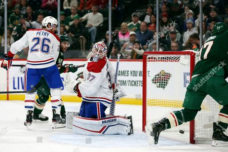 Stock Image of Montreal Canadiens' goalie Keith Kinkaid (37) looks back at the net after Minnesota Wild's Marcus Foligno, right, scored a goal in the second period of an NHL hockey game, in St. Paul, Minn