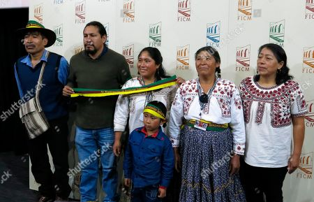 Actors from the Mexican film Sactorum, from left, Javier Bautista, Damian Martinez, Nereida Vasquez, Virgen Vasquez, Ofelia Diaz and Edwin Perez, front, pose with a sign against mega-projects on indigenous lands during a press conference at the Morelia Film Festival in Morelia, Mexico