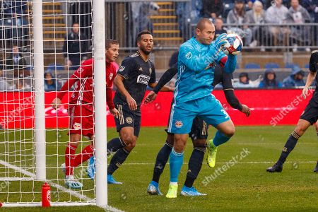 New York Red Bulls' Luis Robles, center, makes a save on a corner kick during the first half of an MLS soccer Eastern Conference first-round playoff match against the Philadelphia Union, in Chester, Pa