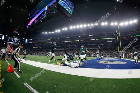 Stock Image of Boston Scott, Nate Gerry, Malcolm Jenkins, Dak Prescott. Dallas Cowboys quarterback Dak Prescott (4) reaches the end zone for a touchdown as Philadelphia Eagles' Nate Gerry (47), Malcolm Jenkins (27), and Orlando Scandrick (38) defend in the second half of an NFL football game in Arlington, Texas