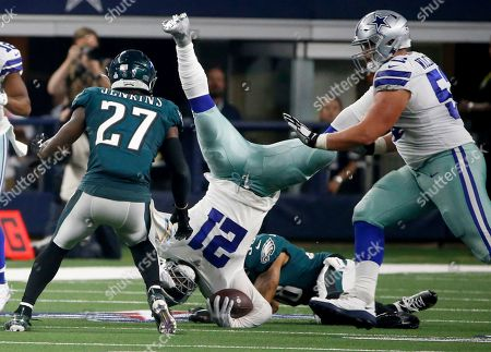 Orlando Scanrick, Connor Williams, Ezekiel Elliott, Malcolm Jenkins. Philadelphia Eagles' Malcolm Jenkins (27) and Dallas Cowboys' Connor Williams, right, look on as running back Ezekiel Elliott, center, is upended by Eagles cornerback Orlando Scandrick, bottom rear, in the second half of an NFL football game in Arlington, Texas