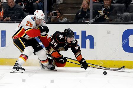Sam Steel, Michael Stone. Anaheim Ducks' Sam Steel (34) trips in front of Calgary Flames' Michael Stone (26) during the second period of an NHL hockey game, in Anaheim, Calif