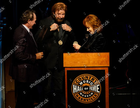 Stock Photo of Reba McEntire,Ronnie Dunn,Kix Brooks. Reba McEntire gives Kix Brooks, left, and Ronnie Dunn, right, their medallions during their Hall of Fame induction at the 2019 Medallion Ceremony at the Country Music Hall of Fame and Museum on in Nashville, Tenn