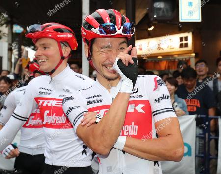 Japanese cyclist Fumiyuki Beppu of Trek Segafredo shows an inch with his fingers as his teammate Edward Theuns of Belgium won the tight race