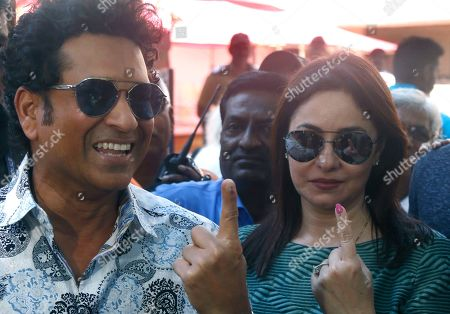Former Indian cricketer Sachin Tendulkar, left, with his wife Anjali pose for media after casting their votes in Mumbai, India, . Voting is underway in two Indian states of Maharashtra in the west and Haryana in the north where the Hindu nationalist Bharatiya Janata Party (BJP) headed by prime minister Narendra Modi is trying to win a second consecutive term