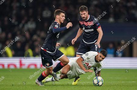 Erik Lamela of Tottenham Hotspur looks to recover the ball after tackling Milos Degenek of Red Star Belgrade
