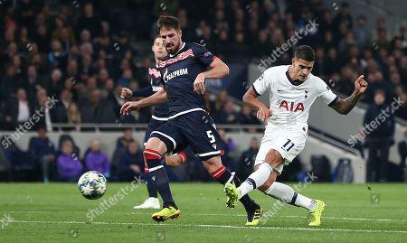 Erik Lamela of Tottenham Hotspur shoots at the goal   under pressure from Milos Degenek of Red Star