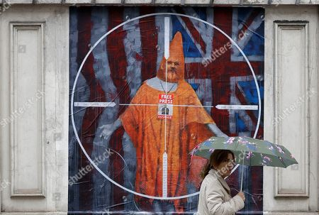 A pedestrian passes street art depicting Julian Assange near Westminster Magistrates' Court in London where Assange is expected to appear as he fights extradition to the United States on charges of conspiring to hack into a Pentagon computer, in London, . U.S. authorities accuse Assange of scheming with former Army intelligence analyst Chelsea Manning to break a password for a classified government computer