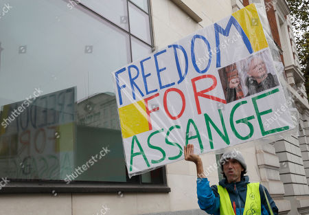 A supporter of Wikileaks founder Julian Assange demonstrates outside Westminster Magistrates' Court in London where Assange is expected to appear as he fights extradition to the United States on charges of conspiring to hack into a Pentagon computer, in London, . U.S. authorities accuse Assange of scheming with former Army intelligence analyst Chelsea Manning to break a password for a classified government computer