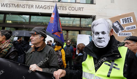 Supporters of Wikileaks founder Julian Assange, seen on mask at right, demonstrate outside Westminster Magistrates' Court in London where Assange is expected to appear as he fights extradition to the United States on charges of conspiring to hack into a Pentagon computer, in London, . U.S. authorities accuse Assange of scheming with former Army intelligence analyst Chelsea Manning to break a password for a classified government computer