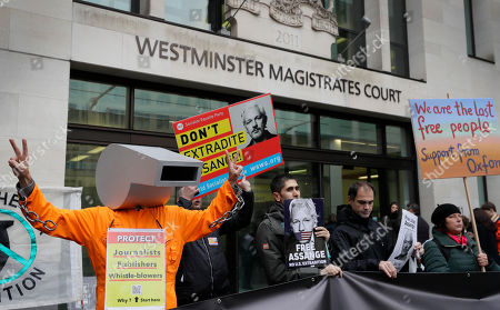 Supporters of Wikileaks founder Julian Assange demonstrate outside Westminster Magistrates' Court in London where Assange is expected to appear as he fights extradition to the United States on charges of conspiring to hack into a Pentagon computer, in London, . U.S. authorities accuse Assange of scheming with former Army intelligence analyst Chelsea Manning to break a password for a classified government computer