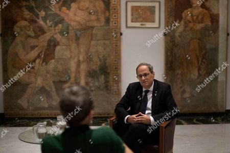 Catalan regional president Quim Torra talks with a journalist at the headquarters of the Government of Catalonia, during an interview with The Associated Press in Barcelona, Spain, . The leader of Catalonia says that the massive protests that have often spiralled into violent clashes with police this week won't cease until the Spanish government accepts to listen to separatists' demands