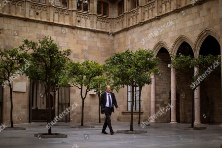 Catalan regional president Quim Torra walks at the Palace of the Generalitat, the headquarters of the Government of Catalonia, ahead of an interview with The Associated Press in Barcelona, Spain, . The leader of Catalonia says that the massive protests that have often spiraled into violent clashes with police this week won't cease until the Spanish government accepts to listen to separatists' demands