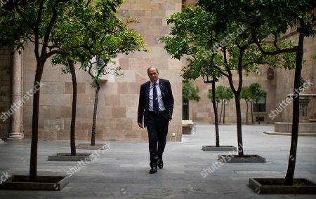 Catalan regional president Quim Torra walks at the Palace of the Generalitat, the headquarters of the Government of Catalonia, ahead of an interview with The Associated Press in Barcelona, Spain, . The leader of Catalonia says that the massive protests that have often spiralled into violent clashes with police this week won't cease until the Spanish government accepts to listen to separatists' demands
