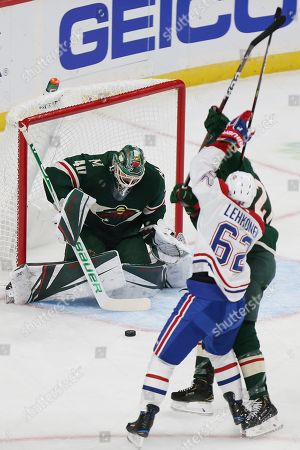 Stock Photo of Minnesota Wild's goalie Devan Dubnyk (40) stops the puck against the Montreal Canadiens in the first period of an NHL hockey game, in St. Paul, Minn
