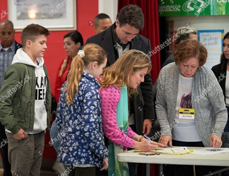 Canadian Prime Minister and Liberal Party leader Justin Trudeau (R) looks on at the polling station for election as his wife Sophie Gregoire signs with their children's Ella Grace, Xavier, and Hadrien in the country's 43rd general election day in Montreal, Quebec, Canada, 21 October 2019.