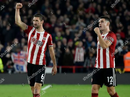 Stock Photo of Sheffield United's Chris Basham, left, and John Egan celebrate after they won the English Premier League soccer match between Sheffield United and Arsenal at Bramall Lane in Sheffield, England