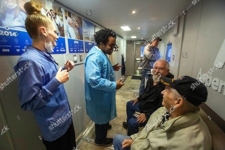 Aspen Dental dental assistant Sam Adams, left, and dentist Dr. David Roberts, center, greets veterans who are waiting inside the lobby of the MouthMobile in Kennewick, Wash. on . The MouthMobile is traveling across the United States providing free dental care to veterans