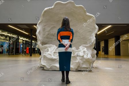 """LONDON, UK. A staff member poses at the entrance to """"Fons Americanus"""" by Kara Walker, which has been unveiled as this year's Hyundai Commission at Tate Modern."""