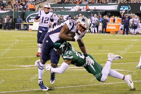 New York Jets' Trumaine Johnson (22) tackles New England Patriots' Benjamin Watson (84) during the first half of an NFL football game, in East Rutherford, N.J