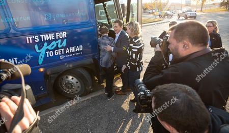 Canadian Conservative Party leader Andrew Scheer (2-L) boards his touring bus with his family outside a voting station after placing his ballot, in Regina, Canada, 21 October 2019.